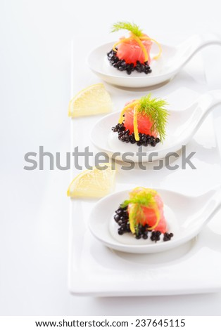 Appetizers in portion spoons of cream cheese, natural sturgeon black caviar, red salted salmon and dill on white table. Selective focus on the middle - stock photo