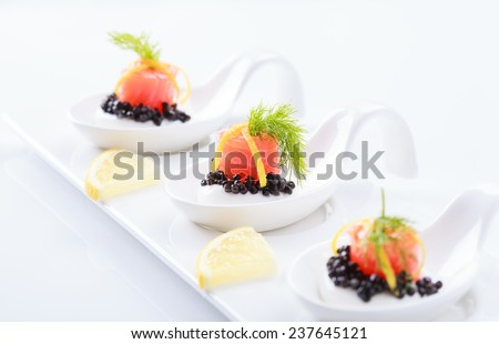 Appetizers in portion spoons of cream cheese, natural sturgeon black caviar, red salted salmon and dill on white background. Selective focus on the middle - stock photo