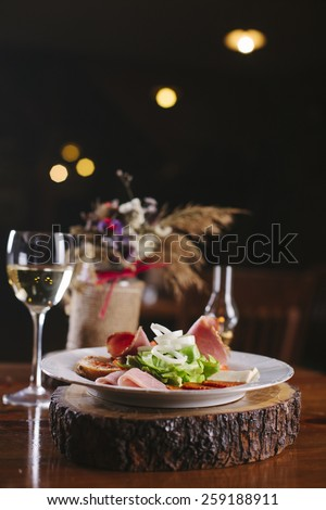 Appetizers - meat and cheese with lettuce and onion  - on wooden board with glass of white wine