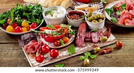 Appetizers on a wooden cutting board.  - stock photo