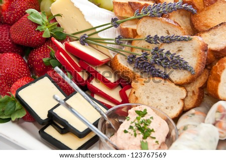 Appetizers selection with strawberries and cheeses on a  platter at an event - stock photo