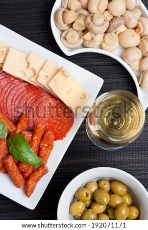 Appetizers set with salami, cheese, mushrooms, olives and kabanos - stock photo
