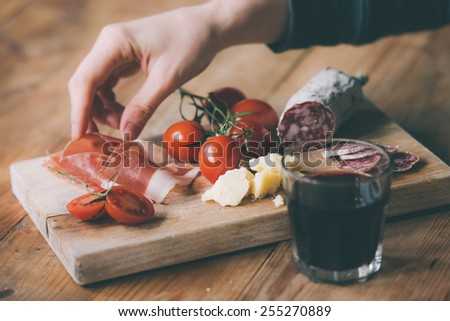 Appetizers - tomato, meat and cheese - on wooden board with  glass of wine. Toned image - stock photo
