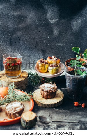 Appetizing baked apples stuffed with raisin and nuts for christmas with vanilla sauce on a old rustic pan on wooden table  - stock photo