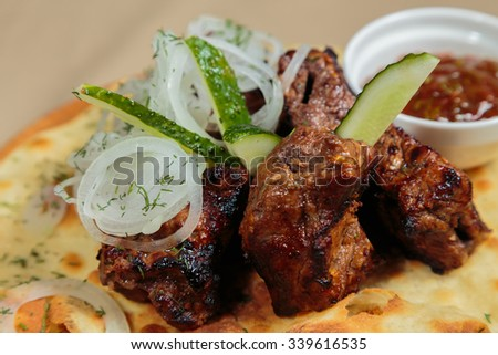Appetizing barbecue cooked with vegetables and sauce served on a wooden tablet. Beautiful exposition Eastern dishes. Fried meat on pita bread. Photo for culinary magazines, posters, and backgrounds.
