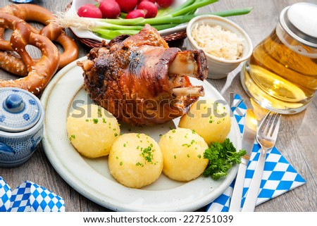 Appetizing Bavarian roast pork knuckle with dumplings and pretzel - stock photo