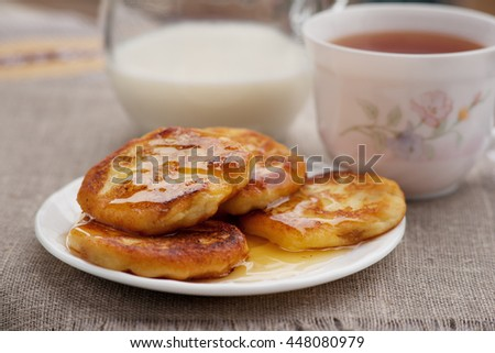 Appetizing cheese cakes with honey, tea and milk on sackcloth.