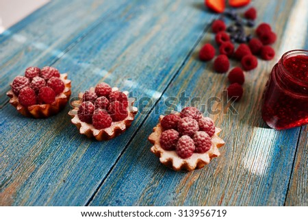 Appetizing delicious basket of unleavened dough are on the table, standing next to homemade jam, housewife smeared  jam tarts and top decorated with fresh raspberries - stock photo