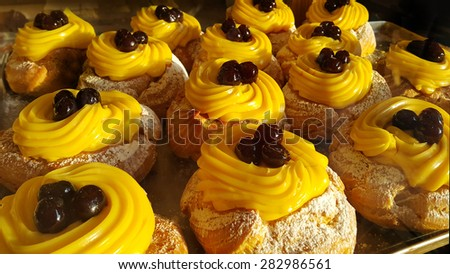 Appetizing eclairs with cream and cherry - stock photo