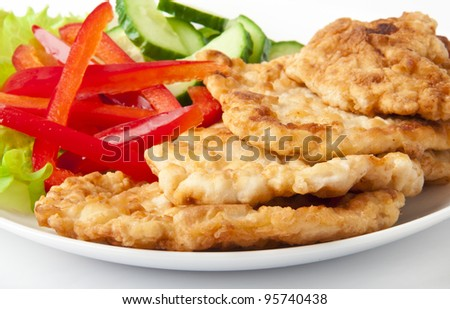 Appetizing fried chicken nuggets with cucumber and pepper on salad leaves. Close-up. Selective focus. - stock photo