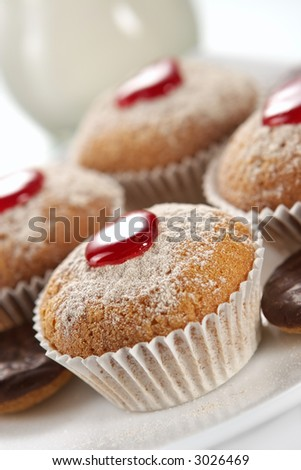 Appetizing fruitcakes and chocolate cookies decorated by powdered sugar and jam - stock photo