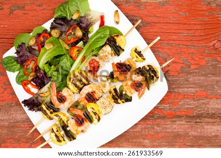 Appetizing Gourmet Shrimp Skewers Served on White Plate with Veggies and Spices on Top of a Rustic Wooden Table, Captured on High Angle View. - stock photo