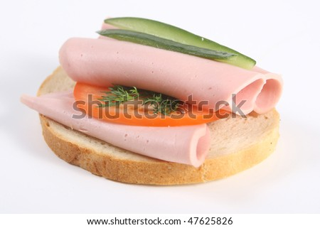 Appetizing ham sandwich with cheese, fresh cucumber and greenery - stock photo