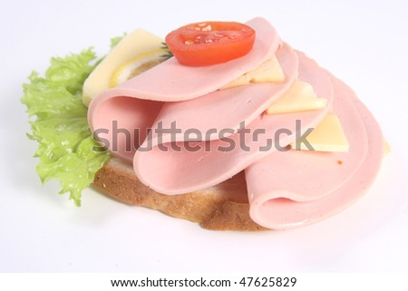 Appetizing ham sandwich with cheese, ripe potato and lettuce - stock photo