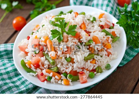Appetizing healthy rice with vegetables in white plate on a wooden background. Selective focus. - stock photo