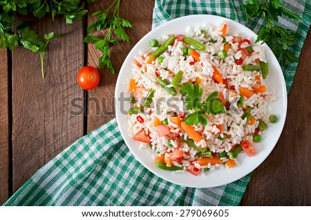 Appetizing healthy rice with vegetables in white plate on a wooden background. Selective focus. Top view. - stock photo