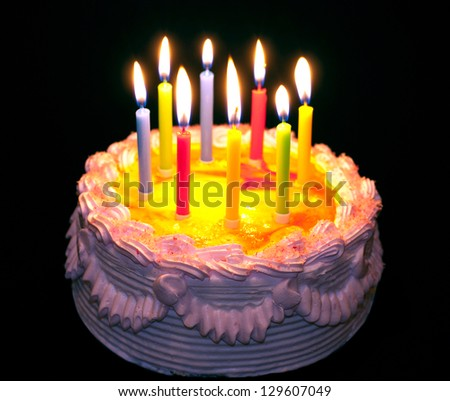 appetizing holiday cake with the light colorful candles against black background - stock photo