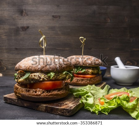 appetizing homemade burgers with chicken in mustard sauce with arugula and herbs on a cutting board with text area on wooden rustic background close up - stock photo