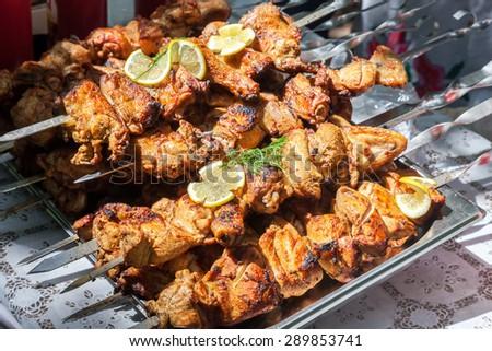 Appetizing hot shish kebab on metal skewers - stock photo