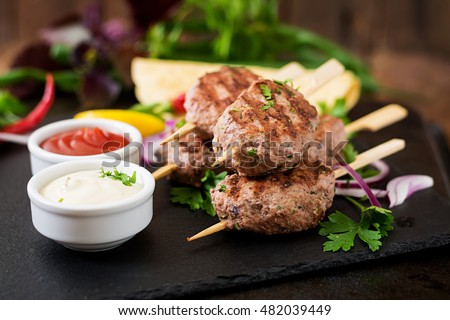 Appetizing kofta kebab (meatballs) with sauce and tortillas tacos on blackbackground