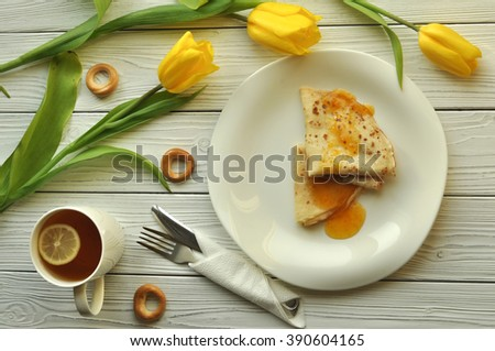 Appetizing pancakes with fruit jam, a cup of tea with lemon, yellow tulips, fork and knife on a rustic white wooden surface