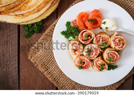 "Appetizing pancakes with salmon and cream cheese ""Philadelphia"". Top view - stock photo"