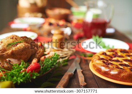 Appetizing pie and roasted chicken on the table