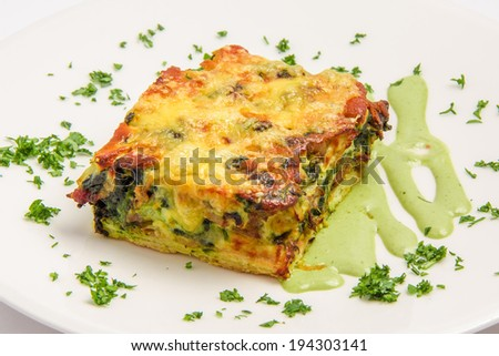 appetizing pie with meat, cheese, vegetables. served with sauce and greens. On white background