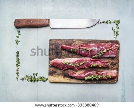 appetizing pieces of raw lamb with herbs and a knife on a cutting board lined rectangle on wooden rustic background top view close up - stock photo