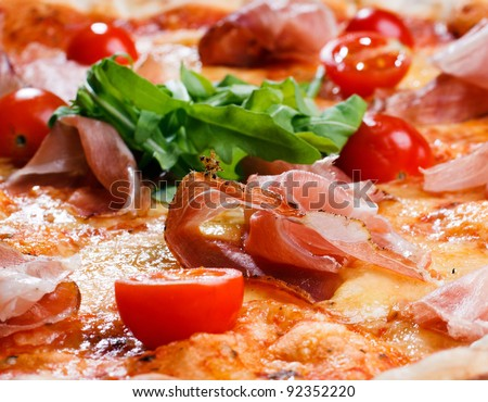 appetizing pizza with ham, tomatoes and greens - stock photo