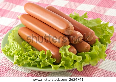 Appetizing pork sausages seasoned by green salad-product for preparation of hot dogs - stock photo