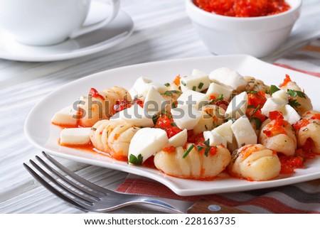 Appetizing potato gnocchi with tomato sauce and mozzarella closeup on the table. horizontal   - stock photo