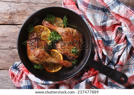 Appetizing roasted duck leg with oranges and parsley in a pan close-up. top view, horizontal, rustic  - stock photo