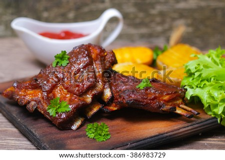 Appetizing rosy and barbecued lamb ribs seasoned with a barbecue sauce and served with fresh herbs and potatoes on an old rustic wooden chopping board - stock photo