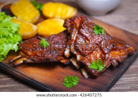 Appetizing rosy and barbecued lamb ribs seasoned with a barbecue sauce and served with fresh herbs and potatoes on an old rustic wooden chopping board