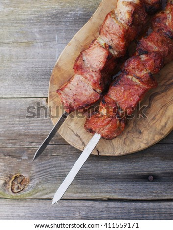 Appetizing shish kebab on skewers on a chopping board on an old wooden surface - stock photo