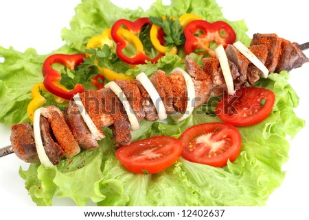 Appetizing shish kebab with tomatoes and greens - stock photo