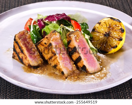 Appetizing slightly roasted tuna with grilled lemon and salad closeup on black background - stock photo