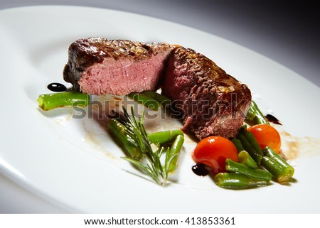 Appetizing stake on white plate. Grilled meat - stock photo