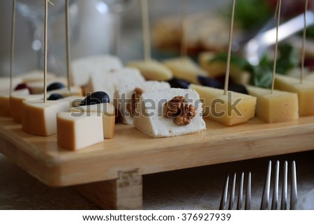 Appetizing tasty beautiful pieces of cheese decorated by fresh walnuts and grapes laying on wooden board plate dairy cuisine food with protein and fat closeup on blur background side view, horizontal  - stock photo