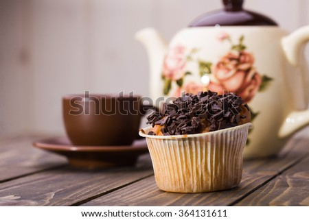 Appetizing tasty fresh muffin in paper basket with chocolate crust on top standing near brown cup of coffee and beautiful teapot on wooden table on light blur background closeup studio, horizontal  - stock photo