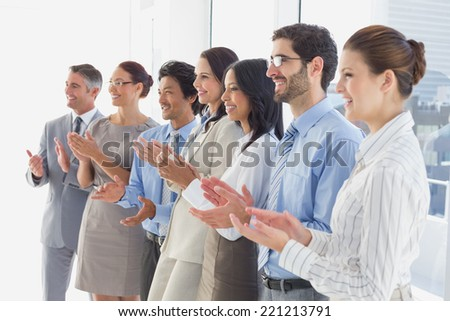 Applauding workers smiling and cheerful at work - stock photo