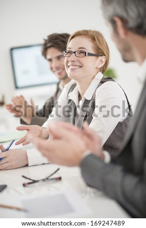 applause for a female colleague in a meeting - stock photo