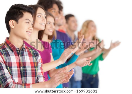 Applause. Group of cheerful young multi-ethnic people standing in a row and applauding to someone while standing isolated on white - stock photo