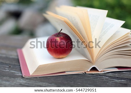apple and a book on a wooden table