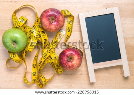 apple and a measuring tape on wooden table with chalkboard - stock photo