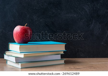 Apple and a stack of books on desk with blackboard in background
