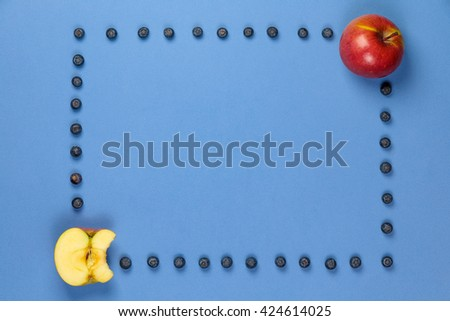 Apple and apple bitten off with frame of blueberries on a blue background. It can be used for advertising of healthy nutrition - stock photo