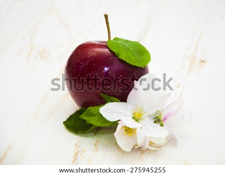 Apple and apple blossom on a white wooden background - stock photo
