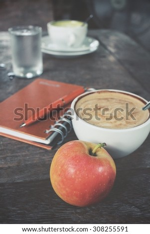 Apple and blank notepad with coffee on office table